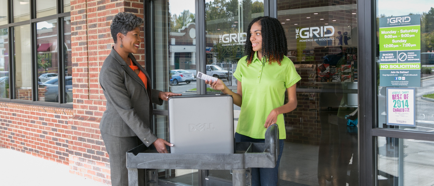 A woman donates a used computer system to The GRID.