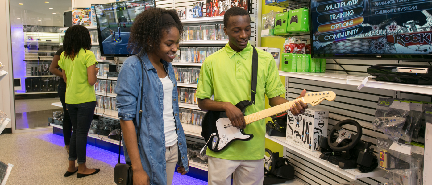 A team member at Goodwill's electronics store, The GRID, shows an item to an interested customer.